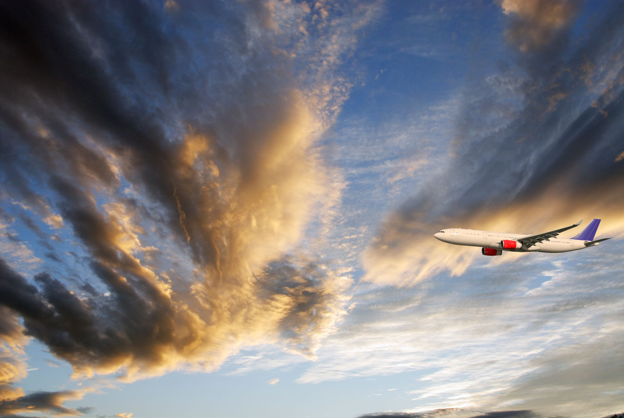 airliner-flying-through-cloud-scapes-blue-sky